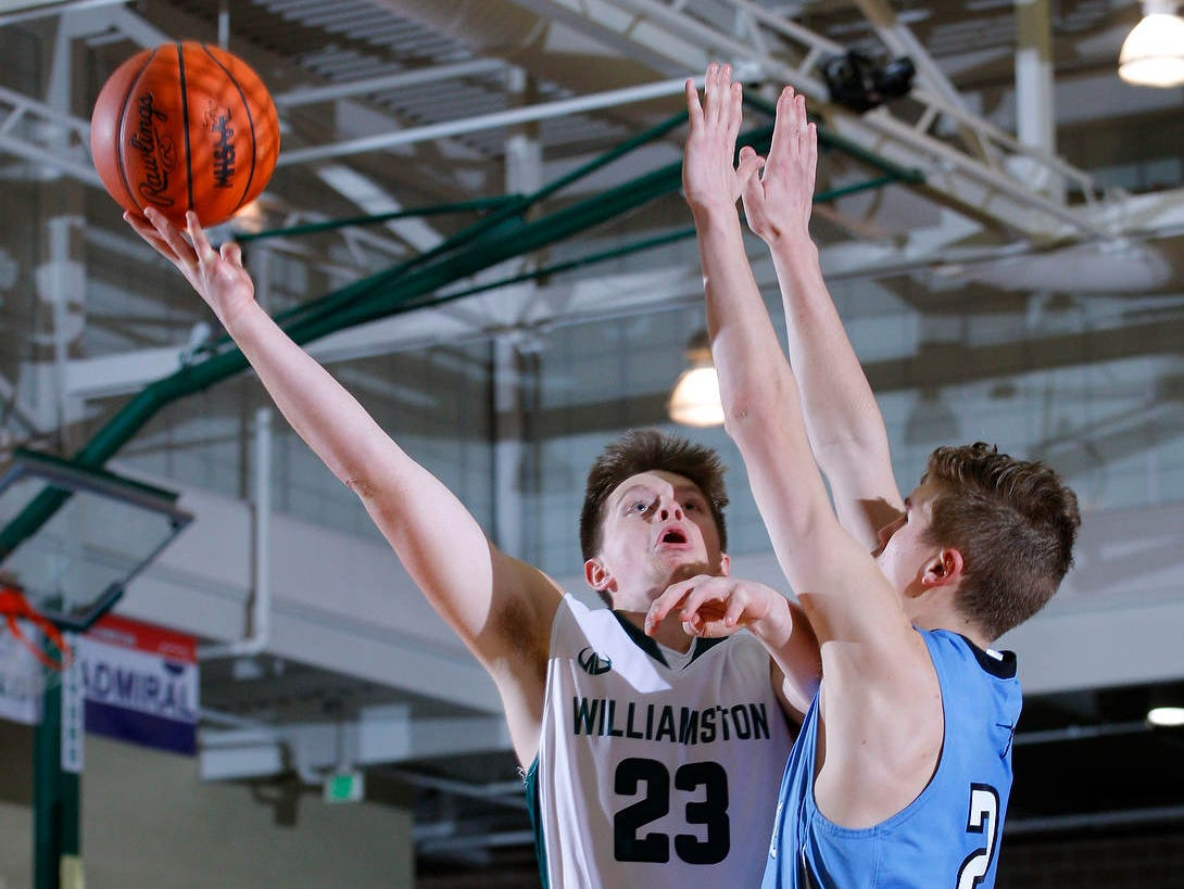 Williamston's Cole Kleiver, left, shoots against Lansing Catholic's Chuck Plaehn Friday, Jan. 27, 2017, in Williamston, Mich. Lansing Catholic won 76-72.