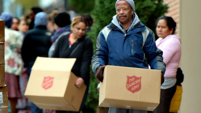 Volunteer Aubrey Brown of York City helped people load their food boxes into cars during the Salvation Army Christmas Cheer Distribution in York City on Monday, Dec. 21, 2015. Salvation Army Director of Social Services David Pillette said the distribution benefits 1,800 families in the area. (Bill Kalina - The York Dispatch)