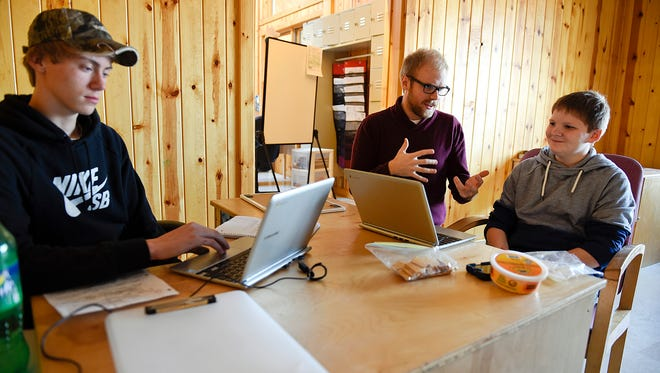Noah Swanson, 15, Monticello, (left) does research on steelhead trout for a project while advisor Eric Lynne (center) works with Colten Lanie, 12, Maple Lake, on his English assignment Wednesday, March 2, at the Jane Goodall Environmental Sciences Academy near Maple Lake.