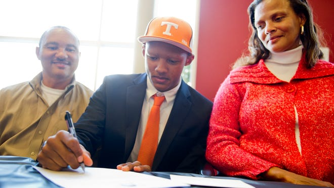 Seated between his father, Robert, and mother, Stephanie, Joshua Dobbs signs his letter of intent to play football at Tennessee on Feb. 6, 2013.