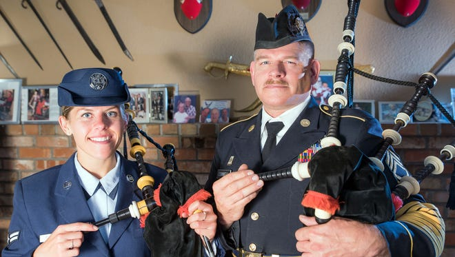 Airman 1st Class Mariah Connel and her father, Sgt. 1st Class Michael Connell, pose for a photo in his living room holding their military bagpipes. Behind them, photos of Michael Connell's family and friends line the mantle and historic military and non-military swords hang on the walls.