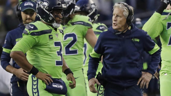 Seattle Seahawks coach Pete Carroll talks with quarterback Russell Wilson (3) during the first half of an Oct. 3 game against the Los Angeles Rams in Seattle.