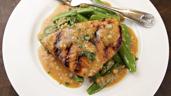Pineapple citrus grilled swordfish with garlic snap peas prepared by Chef Eric Naddy of Sweet Basil.