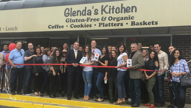 Owner Carmen Petruzzelli and Mayor Gerard Scharfenberger cut the ribbon while family, friends and other local business owners gathered around for the celebration.