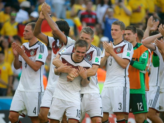 Germany's Philipp Lahm and Bastian Schweinsteiger celebrate after the World Cup quarterfinal soccer match between Germany and France at the Maracana Stadium in Rio de Janeiro, Brazil, Friday, July 4, 2014. Germany won the match 1-0.