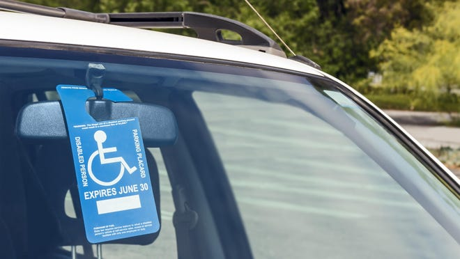 Handicap tag hangs from the rear view mirror of a car.