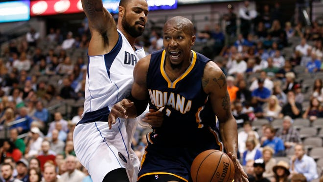 Indiana Pacers forward David West (21) drives the ball around Dallas Mavericks center Tyson Chandler (6) during the first half of a preseason NBA basketball game, Sunday, Oct. 12, 2014, in Dallas, Texas. (AP Photo/Jim Cowsert)
