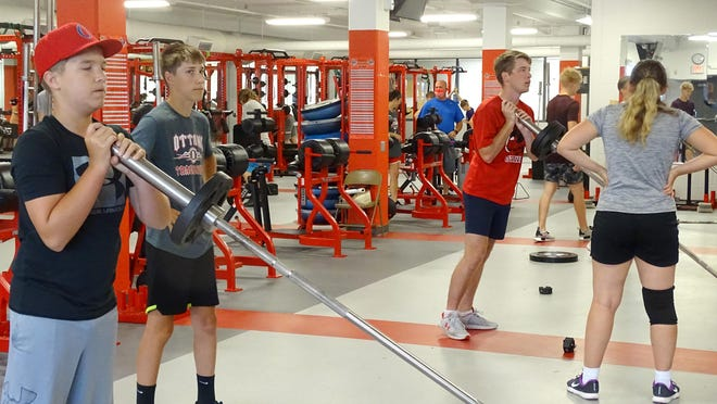 The Ottawa High School students use light weights to stretch out muscles during the first week of conditioning.