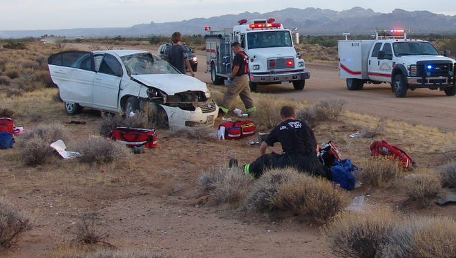 Golden Valley firefighters tend to two teens after a rollover crash near Kingman on Aug. 11, 2015.