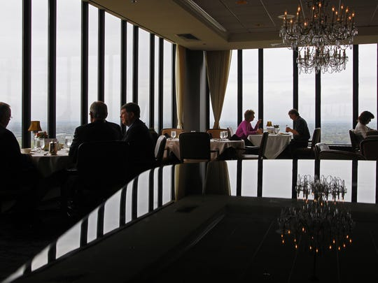 Diners at the Des Moines Embassy Club are reflected on the surface of a grand piano during lunch.