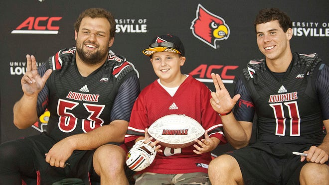 """University of Louisville offensive guard Jake Smith, left, and quarterback Will Gardner, right, hold up their hands in the shape of an """"L"""" as Noah Woosley, 13, of Fern Creek, poses for a photo with them at the Cardinals' Fan Day in Cardinal Arena on Saturday, Aug. 16."""