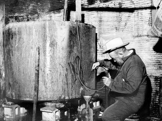 Sheriff Jack Cox siphons off a jug of white lightning from what he said was one of the biggest still operations he'd seen in 10 years in Giles Country. Cox's raiders found the 6,000 gallons of mash working in seven 1,000-gallon aluminum pots in a shed less than a mile from the Pulaski, Tenn.'s courthouse April 20, 1963. The gas-fired pots were unattended.