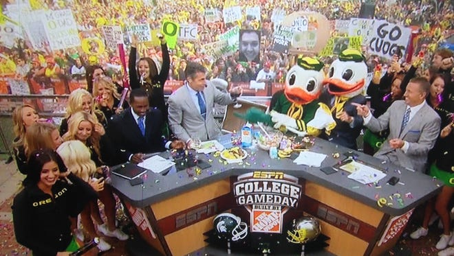 Chris Fowler (second from left) toasts with a glass of wine as he, Desmond Howard (left), The Oregon Duck, Lee Corso (second duck head) and Kirk Herbstreit wrap up Saturday's College GameDay show in Eugene, Ore.
