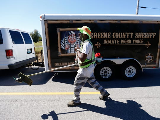 Greene County Jail inmate James Dokes walks with a weed eater on Farm Road 115 to clear brush from around a guardrails on Tuesday, Sept. 27, 2016. Dokes is park of the Greene County Inmate Labor Initiative, a volunteer program for inmates to do the landscaping around the Greene County Justice Center, pick up trash along roadways and clean up after public events.