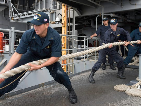 Midshipman 2nd Class Aaron Hobson and Midshipman Christopher Costa assist deck department personnel aboard the USS John C. Stennis. Nineteen midshipmen are on a summer cruise on the carrier.