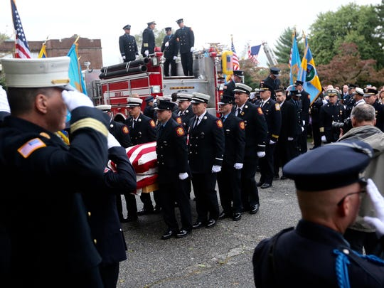 The body of Lt. Christopher Leach is carried in to