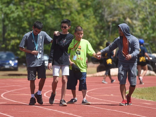 Event competitors receive guidance in the 25 meter assisted walk during the 42nd annual Special Olympics Guam Track and Field competition at Okkodo High School in Dededo on March 17, 2018.