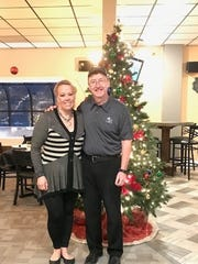 Marcy and Steve Tobalsky stand in front of a Christmas tree at The Jig on opening night, Dec. 6, 2017.