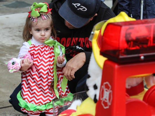Sienna Cabalar, 23 months, is not sure how to react when Boonton's Sparky the Fire Dog starts talking to her during annual Christmas parade on Main Street in Boonton on November 28, 2015.