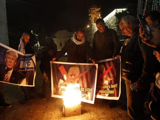 Palestinian protesters burn pictures of President Trump at the manger square in Bethlehem on Dec. 5, 2017.