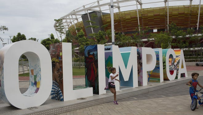 Children play near the Olympic Park sign in Rio de Janeiro, Brazil, where about $12 billion was spent to organize the 2016 games, which were plagued by cost-cutting, poor attendance, and reports of bribes and corruption linked to the building of some Olympic-related facilities.