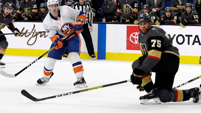 New York Islanders forward Mathew Barzal (13) watches his shot as Vegas Golden Knights right wing Ryan Reaves (75) defends during the third period of an NHL hockey game Saturday, Feb. 15, 2020, in Las Vegas. The Golden Knights won 1-0.