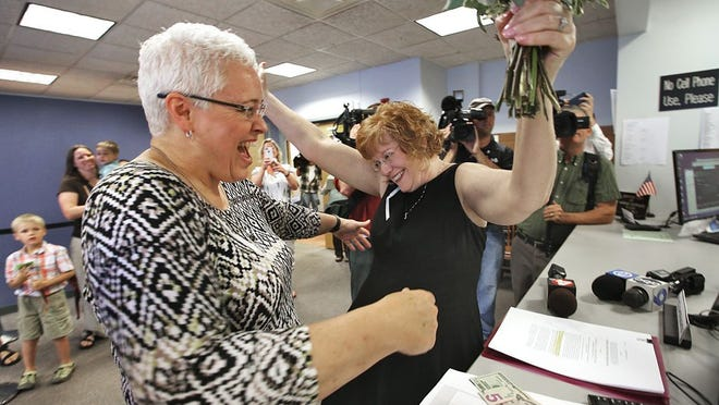 Mindy Ross (left) and Jimmie Beall celebrate at the counter after putting down their money to receive a marriage license at Franklin County Probate Court on June 26, 2015.
