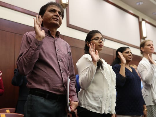 Dilipbhai Bhaichandbhai Patel, left, is sworn in with 74 fellow naturalized citizens by the U.S. Citizenship and Immigration Services during a ceremony at the U.S. District Court downtown on Thursday, May 17, 2018.