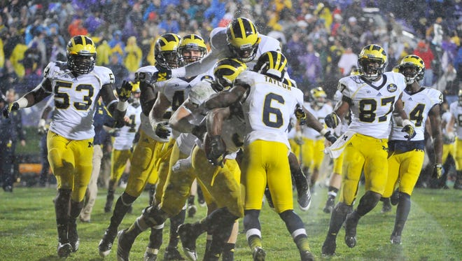 The Michigan Wolverines celebrate their triple-overtime win against the Northwestern Wildcats at Ryan Field.