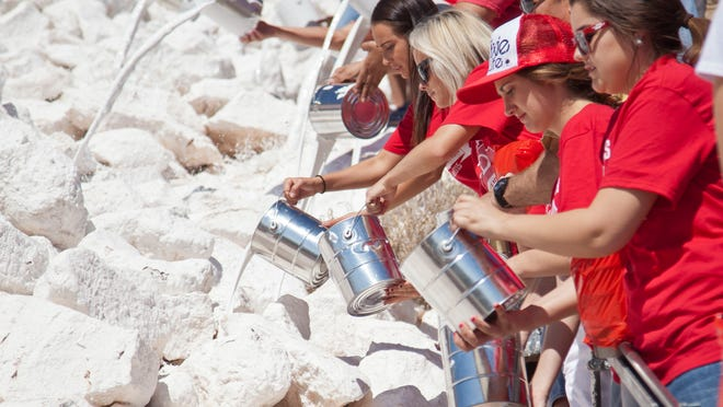 """Dixie State students, faculty and members of the community whitewash the """"D"""" in commemoration of the 100th anniversary of the original painting. Saturday, April 18, 2015."""