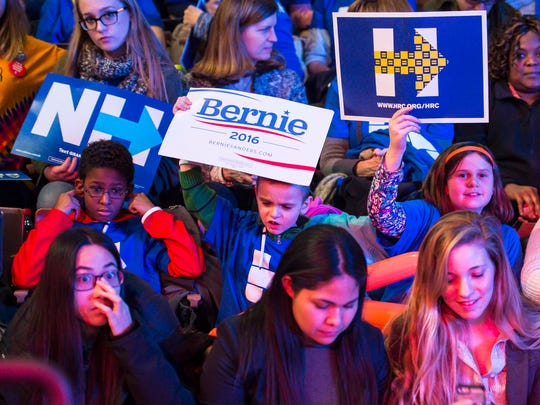 Young audience members have different reactions as supporters of rival Democratic presidential candidates Bernie Sanders and Hillary Clinton trade chants at the New Hampshire Democratic Party's 2016 McIntyre-Shaheen 100 Club Celebration at the Verizon Wireless Center in Manchester on Friday, February 5, 2016.