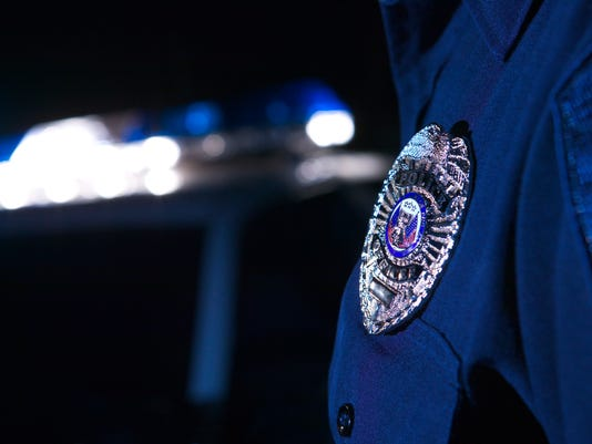 Close-up of an officer's badge with the police lights on the car flashing in the background