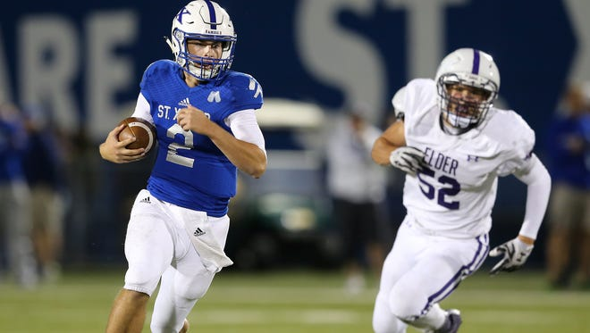St. Xavier quarterback Chase Wolf (2) escapes the pocket in the fourth quarter during the high school football game between the Elder Panthers and St. Xavier Bombers, Friday, Sept. 29, 2017, at at St. Xavier High School in Springfield Township, Ohio.