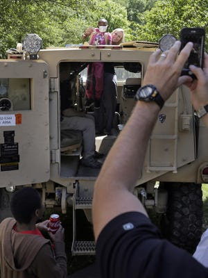Batson Children's Hospital patient KaMiya Watkins, 11, is lifted through the roof of a MRAP armored vehicle at Batson Children's Hospital Monday.
