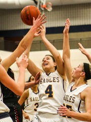 Hartland's Emily Messner (4) pulls down a rebound in the Eagles' victory of Pinckney on Friday night.