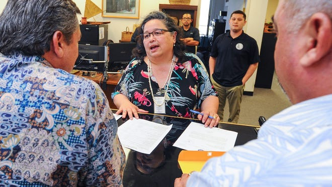 In this file photo, Guam Election Commission Executive Director Maria Pangelinan, center, explains the procedure and requirements needed in filing a referendum to Gov. Eddie Calvo, left. Calvo wanted to submit a draft measure to petition for a referendum on the political status plebiscite.
