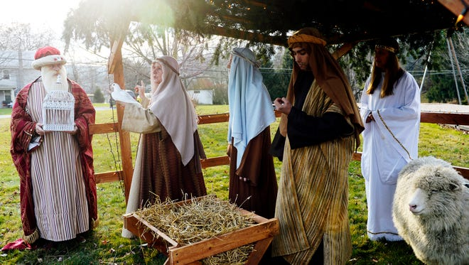 Kathy Ammerman, second from left, holds a dove while directing a nativity rehearsal with Nelson Swarts of Newberry Township, left, Rachel Logue of Mechanicsburg, Trevor Anspach of Newberry Township, Dot Helmick of Newberry Township and a sheep named Butters outside the Lewisberry Community Center. The live nativity will be performed following a parade on Dec. 20.