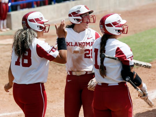 Oklahoma's Grace Green, middle, screams as she high-fives Jocelyn Alo, left, next to Nicole Mendes, right, after Green and Alo scored in the third inning against Texas Tech during a Big 12 softball tournament game in Oklahoma City, Friday, May 10, 2019. Oklahoma won 8-0 in six innings. (Nate Billings/The Oklahoman via AP)