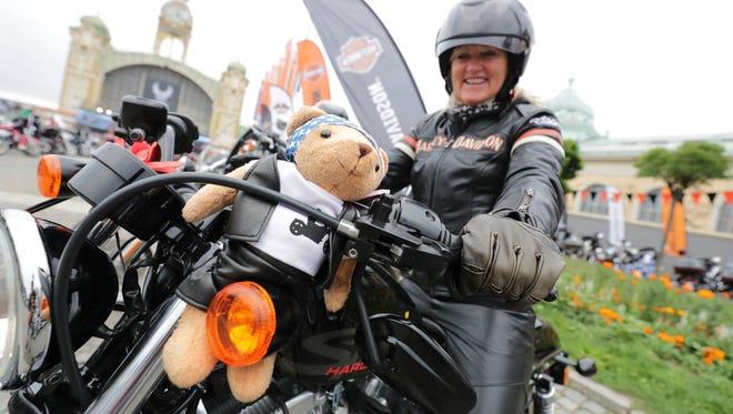 A Harley rider sports a stuffed animal on her Harley.