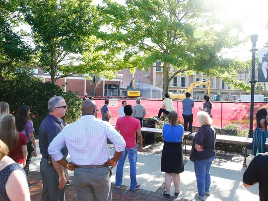 Faculty, staff, and students watch as construction