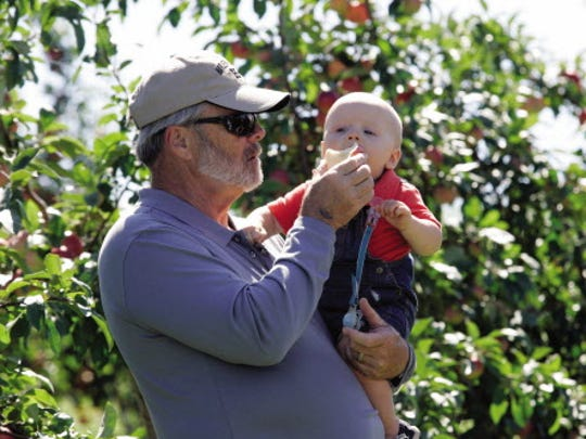 Dave Eberle, of Racine, continues a family tradition with his grandson, 10-month-old Alexander Eberle during the annual Autumn Harvest Festival at the Elegant Farmer.