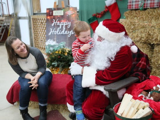 Santa visits with a child at the Christmas Express Train event at the Elegant Farmer.