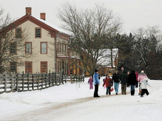 Visitors to Old World Wisconsin for an Old World Christmas enjoy a snowy 1870s Crossroads Village.