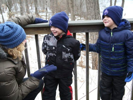 Levi Hammer, 5, center, and his brother Brady, 6, turn