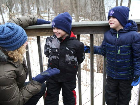 Levi Hammer, 5, center, and his brother Brady, 6, turn to their grandmother, Cheryl Kornburger and giggle at the Wehr Nature Center Winter Wonderland Walk.