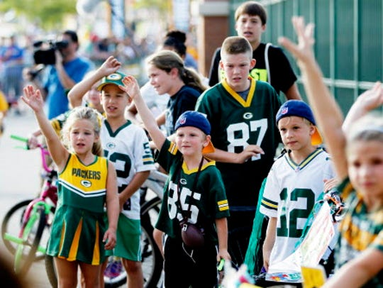 Kids eagerly wait a Packers player to pick their bike