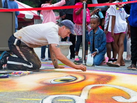 Seth Christian Sanders works on a street chalk mural while children watch.