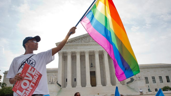 Carlos McKnight, 17, of Washington, holds up a flag in support of gay marriage outside of the Supreme Court in on June 26, 2015.