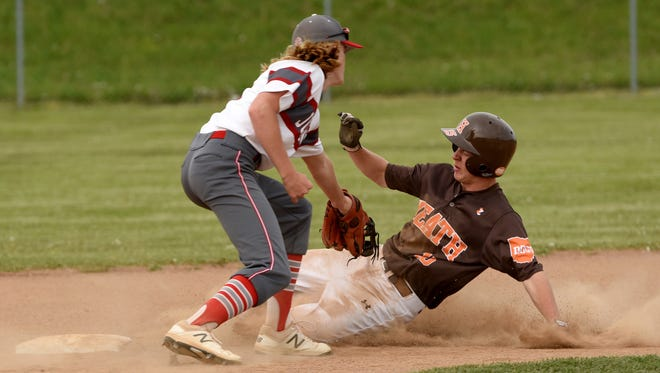 Johnstown shortstop Peyton Clift tries to tag out Heath's Austin Morrow. The Johnnies defeated the Bulldogs 5-2 on Friday, April 28, 2017.