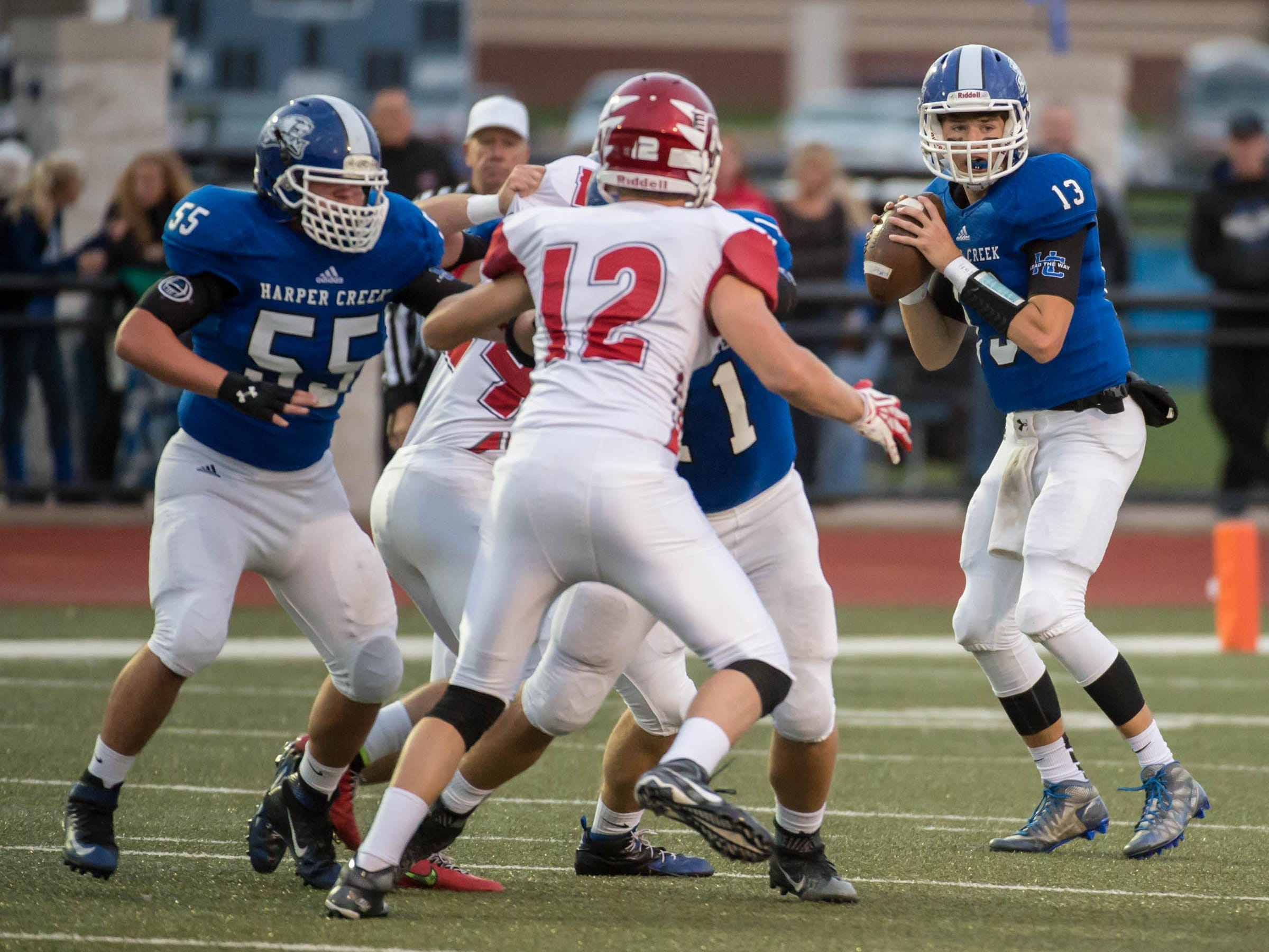 Harper Creek's David Thompson (no. 13) looks for a reciver down field against Coldwater Friday evening.